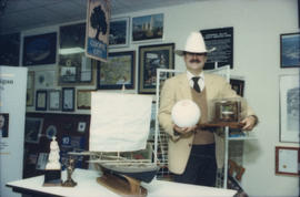 Mike Harcourt posing in a cowboy hat in front of gift display