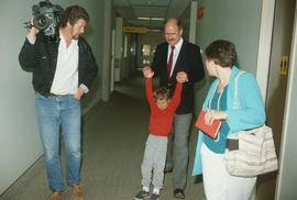 Mayor Harcourt, his family, and cameraman in hospital corridor during visit  with the Vancouver C...
