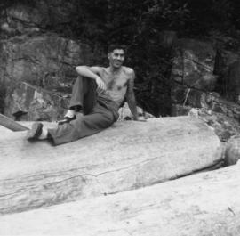 Unidentified man seated on driftwood