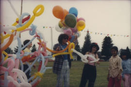 Balloon twisters entertaining group of children