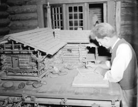 [Man writing in a ledger beside a model log cabin at Silver Creek Camp]