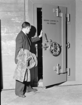 [Man with fur coat entering the fur storage vault at Nelsons Laundry]