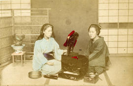 [Studio portrait of two women in traditional Japanese dress sitting on floor with small vanity ta...