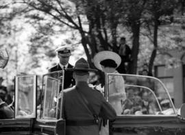 [An R.C.M.P. officer assists King George VI and Queen Elizabeth to get into a car]