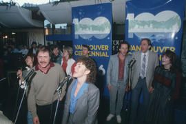 People singing into microphones at Vancouver's 99th birthday celebration