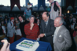 Pat Carney, Mike Harcourt and unidentified cutting cake for Vancouver's 99th birthday celebr...
