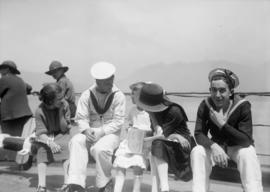 Sailors with a woman and children on the deck of a ship