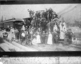 [Group of men, women and children assembled on and around C.P.R. passenger train]
