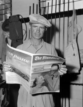 "[Man reading ""The Standard"" newspaper]"