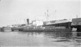 M.S. Ravnass [at dock, with lumber-filled barges alongside]