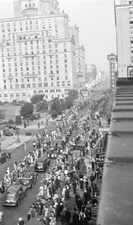 [Parade of cars passing by crowds along Georgia Street]
