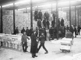 [Soldiers move boxes of food  for the Western Front in a store house]
