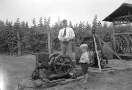 [Man and boy standing near a piece of farm machinery]