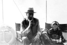 [L.D. Taylor sitting on board the ship [Cora?] May with a young girl]