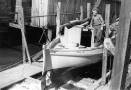 Karl Koenig standing on boat in front of Harbour Marine Service building