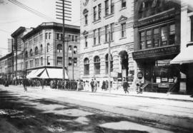 [View of 500 block of Pender Street, showing commercial buildings and pedestrians assembled on si...