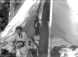 [Two women seated in front of tent at Greer's Beach (Kitsilano Beach)