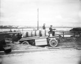 [Men using a storage battery operated truck to haul reels of cable at the south side of False Creek]