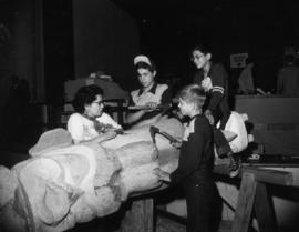 Kwakiutl carver Ellen Neel and three boys carving a totem pole