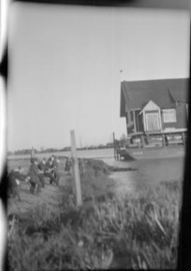 [Men pulling Baptist Church on a barge towards the shore of the Fraser River]