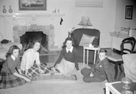 [Teenagers seated on a living room floor with a game]