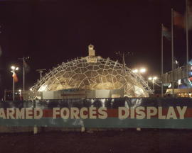 [Armed forces display building at the P.N.E. lit up at night]