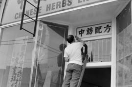 Man painting a sign at the new Chinese Herbs Enterprises store on the 200 block of East Hastings ...