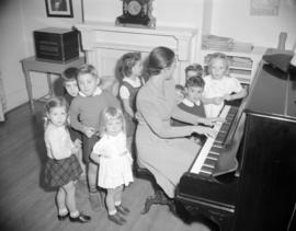 [Woman from the Junior League playing the piano for some children]