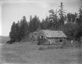 [Woman standing in front of log cabin in interior dry belt]