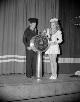 "[Woman in a sailor suit with a navy man on stage at the Orpheum Theatre to promote the ""Meet..."