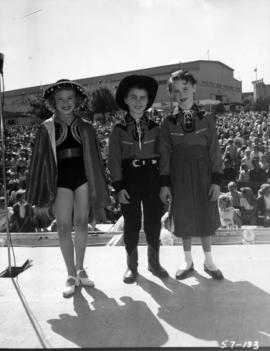 Children in costume on Outdoor Theatre stage with crowd and Commercial building in background