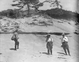 [Three unidentified people on a beach]