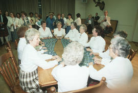 Group of women wearing kilts seated at table holding a piece of Centennial tartan fabric
