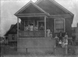 [The Davidson and Hutchinson families on the porch and steps of a house on 29th Avenue near Frase...