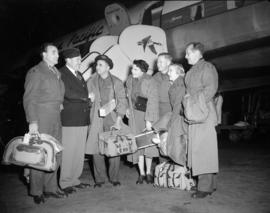 [Members of the Civilian Concert Party waiting to board a Canadian Pacific airplane]