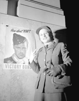 Private Underhill [C.W.A.C., in front of a] Victory Bond poster