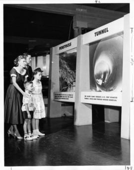 Family looking at hydroelectricity exhibit in P.N.E. B.C. building