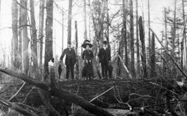 [A woman and two men standing on a fallen log in a forest]