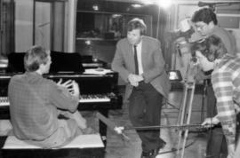 Man seated at piano in recording studio