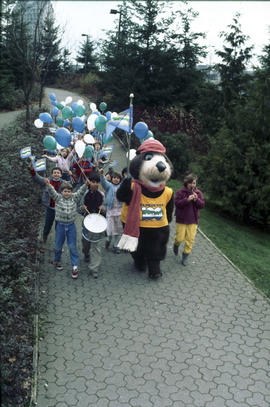 Tillicum walking with group of children holding Centennial flags and balloons