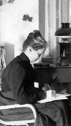 [Caroline Little Pierce sitting by a table writing a note]