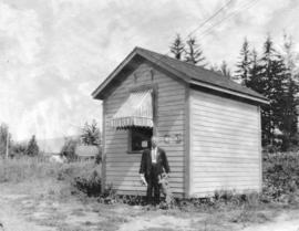 [William Martin and his dog in front of the Imperial Oil Company storage shed]