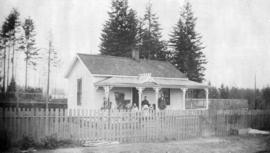 [James Hutson and family in front of cottage on the northeast corner of Cemetery (North Arm) Road...