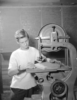 Boy using saw [at the] Community Chest Kimount Boy's Club