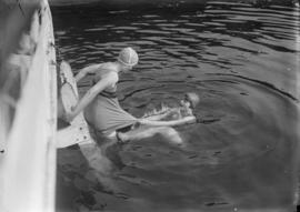 Two women swimming off a dock