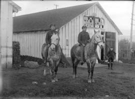 [Soldiers on bareback horses in front of barn]