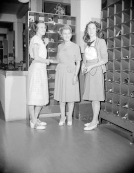 [Three B.C. Telephone operators standing by the headset storage area]