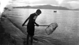 A young boy smelt fishing with a net