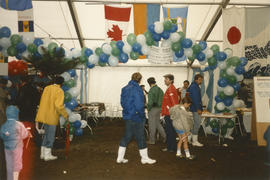People gathered between the Japan and Barbados tables inside the Heritage Showcase tent