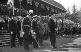 Group of men, some in uniform, standing in front of crowd at Brockton Point Grandstand during Gol...